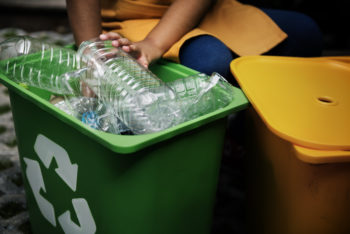 boy sorting through recycling bin