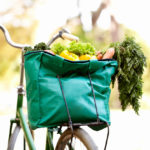 A bike with a reusable bag full of groceries, demonstrating a great way to avoid single-use items