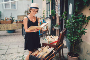 A girl buying a secondhand book, which is a great eco-friendly entertainment option