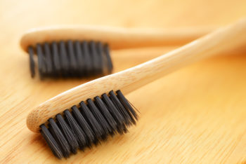 an image of two bamboo toothbrushes on a wooden table