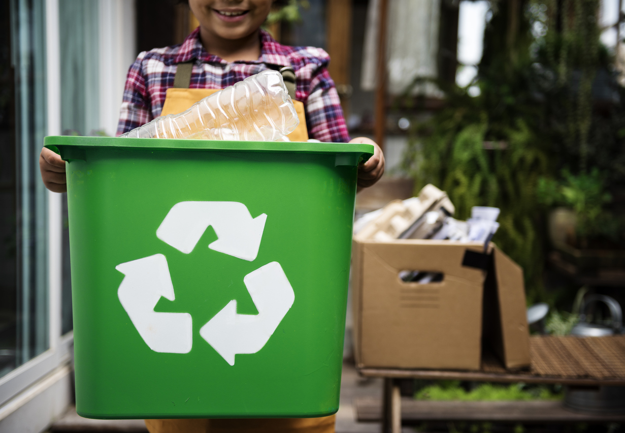 a child holding a recycling bin in an apartment