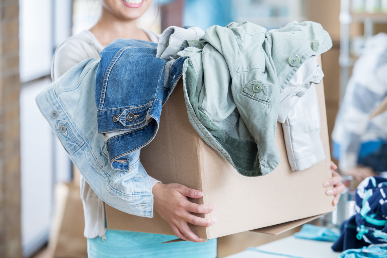 woman donating her old clothes that are in a box