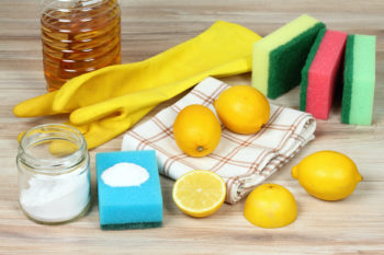 eco-friendly cleaning supplies including lemons, a towel, and thick rubber gloves