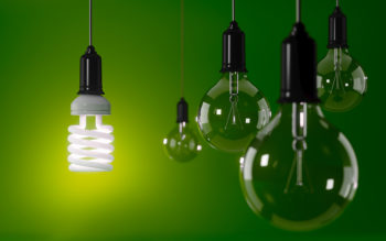 Energy saving light bulb is standing out from the crowd over green background. Energy efficiency concept. Horizontal composition with copy space.