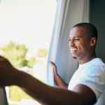 man opening the window for fresh air and light