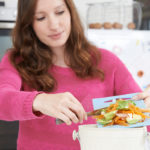 woman-scraping-vegetable-peelings-into-at-home-compost-bin