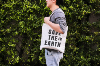 """Young man with a reusable grocery tote that reads """"save the earth"""" slung over his shoulder. reduce kitchen plastic"""