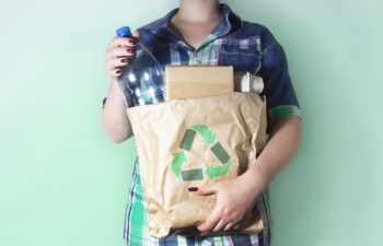 Woman holding a bag of recycling to reduce waste