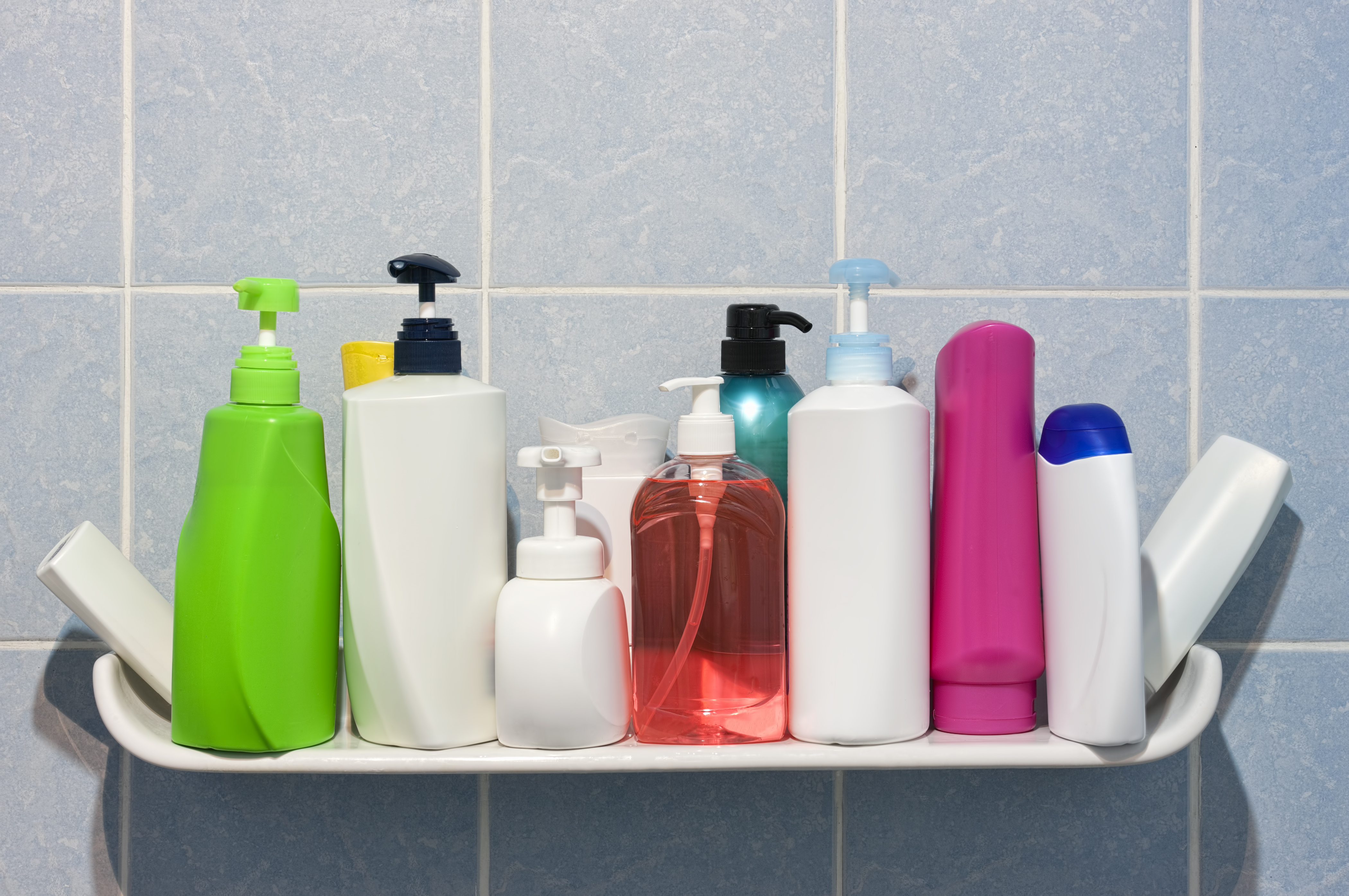 Single-use plastic bottles organized on a shelf in the shower