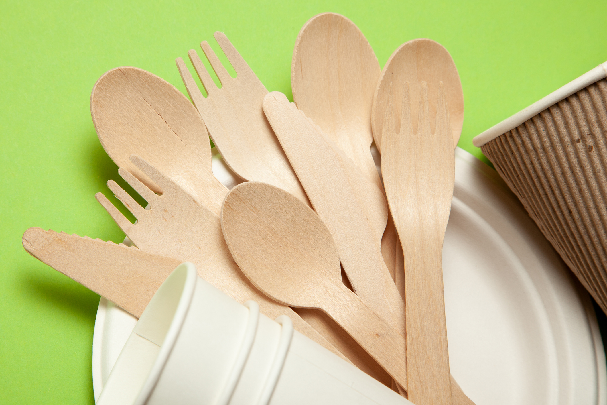 Eco-friendly disposable utensils made of bamboo wood and paper on a green background.
