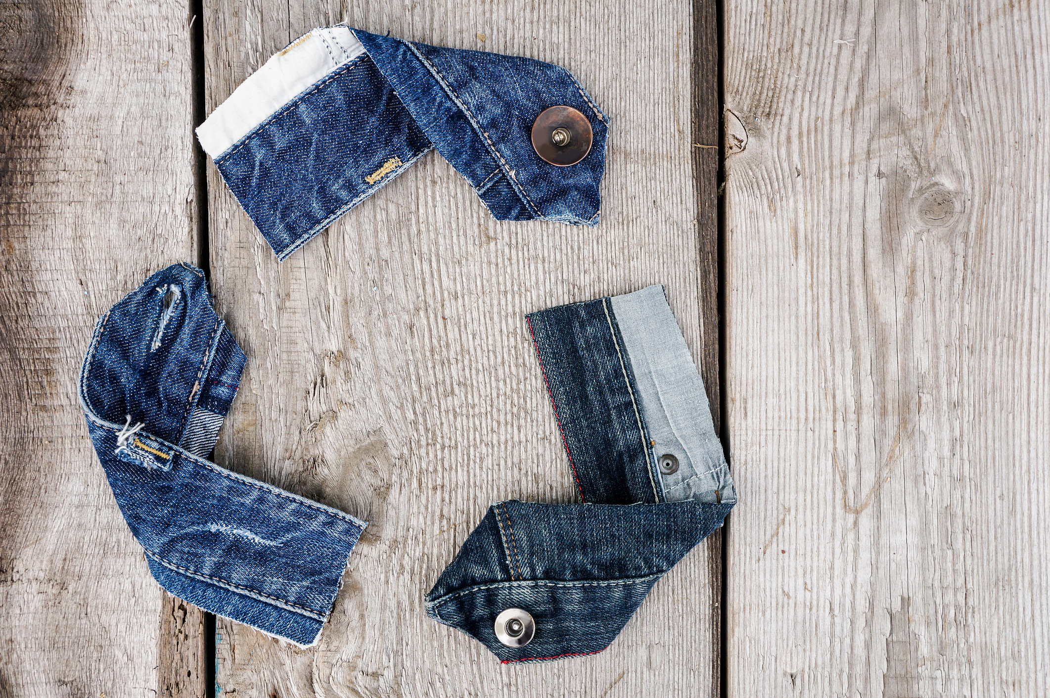 Denim scraps for upcycling arranged into a recycling logo
