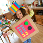 Young girl standing in a kitchen in homemade cardboard robot eco-friendly halloween costume