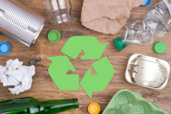 Recycling icon surrounded by recyclable garbage