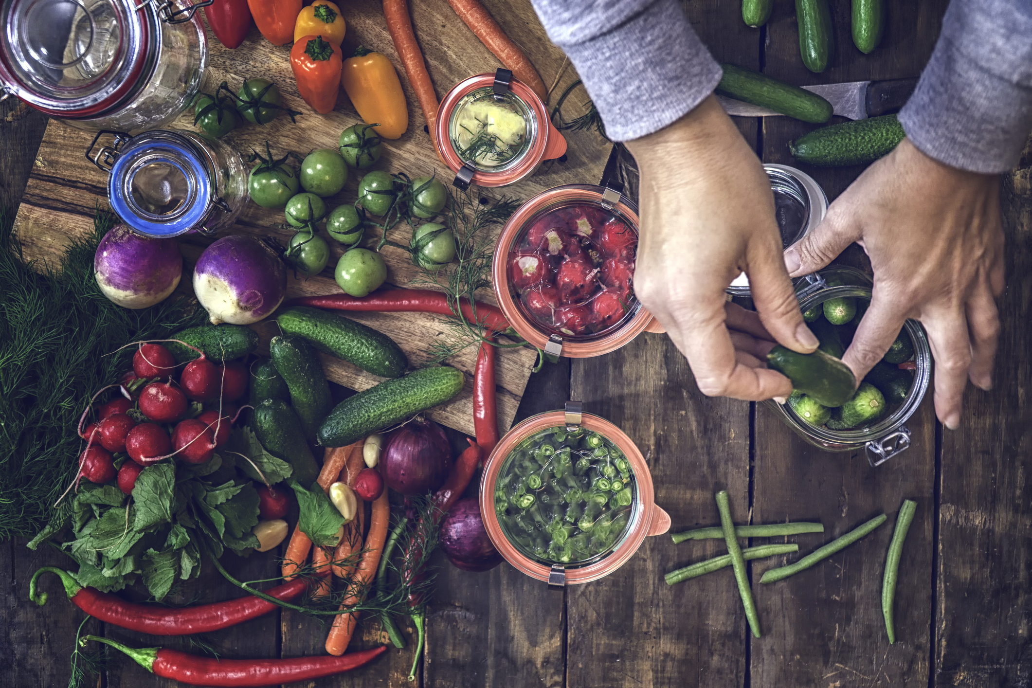 Preserving and canning food and vegetables in jars like carrots, cucumbers, tomatoes, chilis, paprika and radishes.