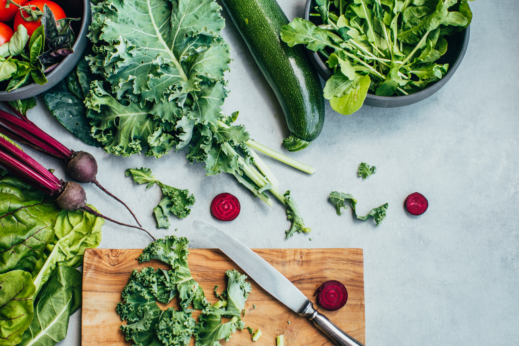 Fresh vegetables like kale and radishes on a cutting board. Eating salad is one way to make eco-friendly choices when going out.