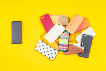 Pile of multicolored plastic Recycled products. They are cases for mobile phones on yellow background with a phone on the side